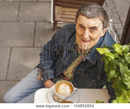Disabled man with cerebral palsy sitting an outdoor cafe.
