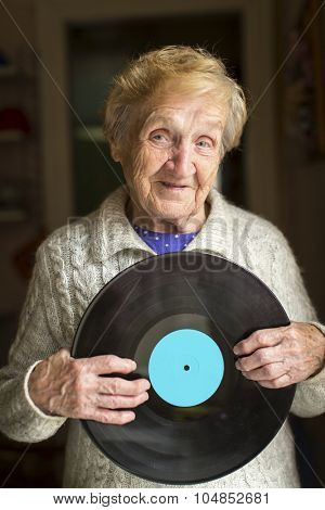 Old woman holding an old LP vinyl record.