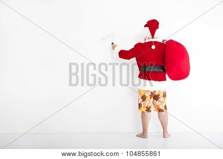 Santa Claus With Beachwear And Painting On The White Wall