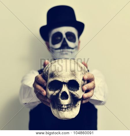 a young man with calaveras makeup, wearing top hat, holds a scary skull in front of him