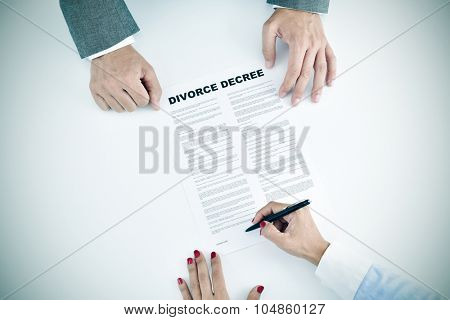high-angle shot of a young woman signing a divorce decree document in front of a young man