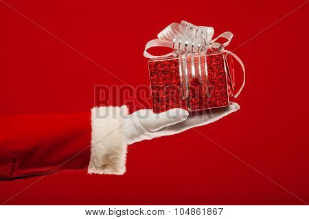 Photo of Santa Claus gloved hand with  giftbox, on a red background