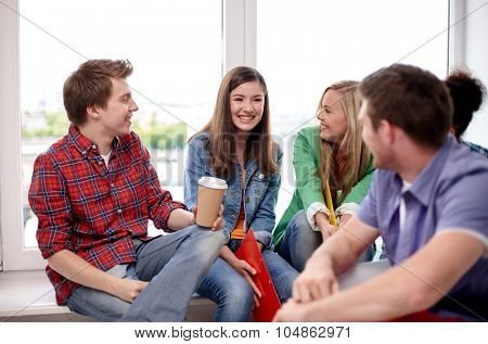education, people, friendship, communication and learning concept - group of happy international high school students or classmates with folders and coffee talking