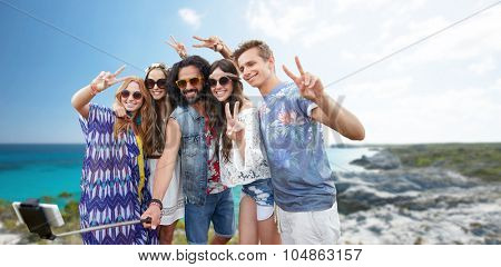summer holidays, vacation, travel, technology and people concept - smiling young hippie friends taking picture by smartphone on selfie stick and showing peace gesture over beach background