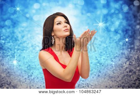 people, holidays, christmas, magic and fashion concept - beautiful sexy woman in red dress blowing fairy dust off over blue glitter or lights background