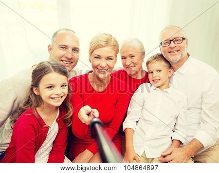 family, holidays, generation, christmas and people concept - smiling family with camera and selfie stick making picture at home
