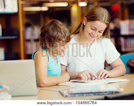 Teenage girl  and her brother with books studying in library