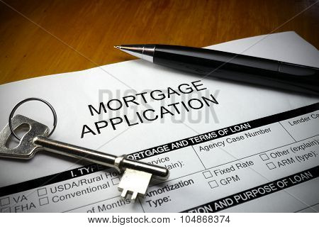 pen and key lying across a mortgage application document