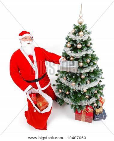 Santa Claus Offering Present In Front Of Christmas Tree