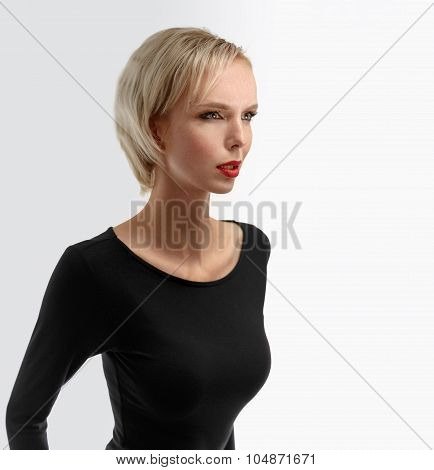 Portrait Of A Beautiful Blonde Woman In A Black Dress.