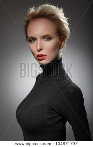 Portrait Of A Beautiful Blonde Woman In A Black Sweater.
