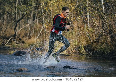 Young man runner splash water in river, during crossing a mountain river