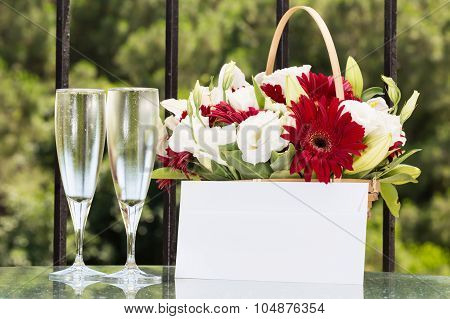 Two Glasses Of Champange And Flower Basket With Plain Envelope