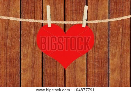Red Heart Hang On Clothespins Over Brown Wooden Planks Background