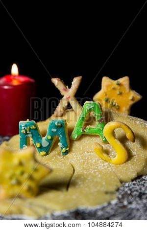Cookie Letters With Cookie Dough And A Candle, Word Xmas With Stars In Front Of Black Background
