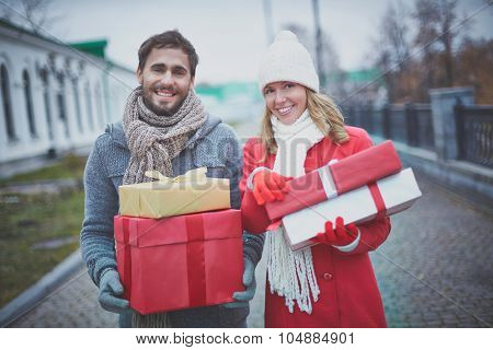 Amorous dates with giftboxes looking at camera outside