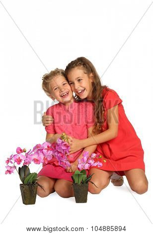 Portrait of two happy girls with orchids in pots isolated on white