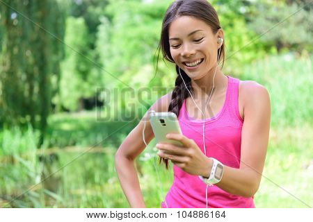 Woman runner sharing running data on social media after exercise. Girl listening to music on smart phone after jogging run in city park. Female jogger with earphones, smartphone and heart rate monitor