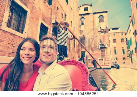 Travel couple in Venice on Gondola ride romance in boat talking happy together on travel vacation holidays. Young multiracial couple sailing in venetian canal in gondole. Italy, Europe