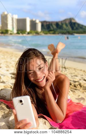 Smart phone woman using smartphone app on beach smiling laughing having fun. Girl reading or messaging or browsing on internet smiling happy outdoors. Mixed race female model on Waikiki Oahu, Hawaii.