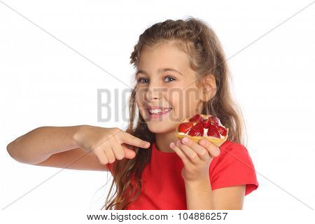 Little girl in a red dress shows a finger on a cake with strawberries isolated on white