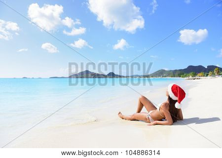 Christmas beach woman wearing santa hat and bikini on holidays travel vacation getaway travel relaxing on tropical beach lying in the sand. Beautiful young female model.