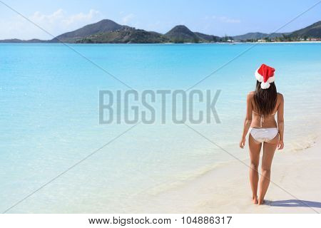 Woman in Santa hat on beach travel vacation getaway enjoying view of tropical beach turquoise paradise beach in the Caribbean. Beautiful girl in bikini under the sun.