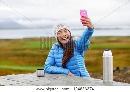 Woman outdoors using smart phone taking selfie photo on app on smartphone while sitting outside wearing warm down jacket. Pretty young mixed race Asian Chinese Caucasian woman in active lifestyle.
