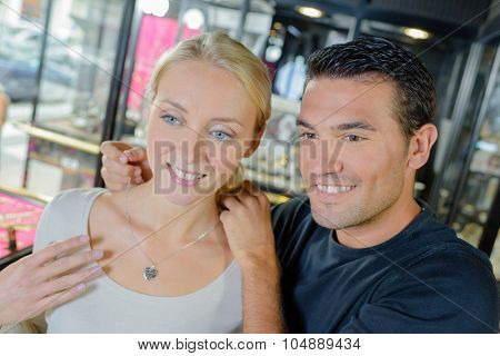 Couple in jewelers, trying on necklace