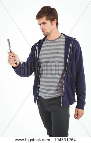 Man holding straight edge razor while standing against white background