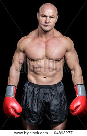 Portrait of bald man with boxing gloves against black background