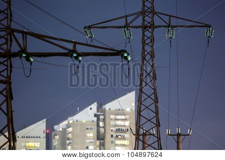High power electricity poles in urban area at night