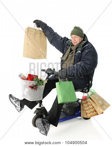 A bundled senior man on a scooter loaded with Christmas gifts.  He's delightedly holding up the largest of the gift bags.  On a white background.