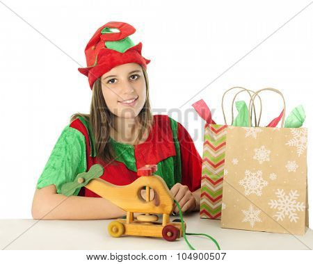 A pretty teen elf smiling at the viewer from behind a table with a toy wooden helicopter and two gift bags.  On a white background.