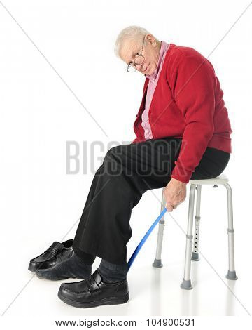 Full length view of senior adult looking at the viewer as he puts his loafers on with a long-handled shoe horn.  On a white background.