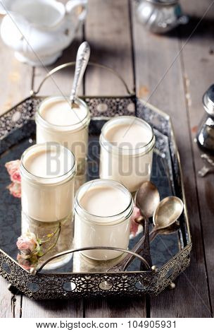 Greek yogurt in glass jars on a metal vintage tray