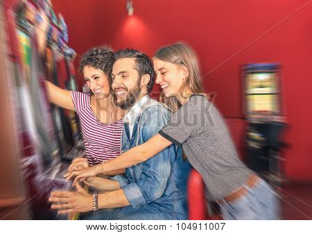 Happy Young Friends Having Fun Together With Slot Machine - Gambling Concept With People at Casino