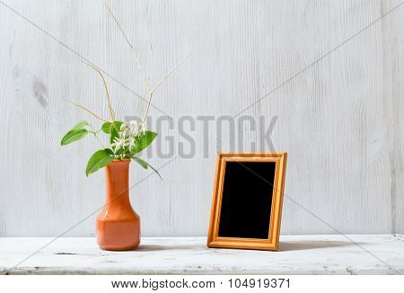 photo frame and flowers on old white table