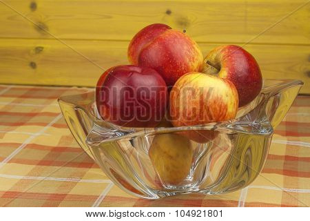 Red apples in a glass bowl on the kitchen table. Healthy food on the table.