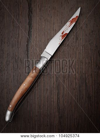 Knife On Wooden Background With Blood On The Blade