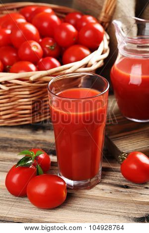 Fresh Red Tomatoes In Basket And Tomato Juice In Glass On Brown Wooden Table
