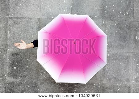 Image of a woman under umbrella checking if it's raining