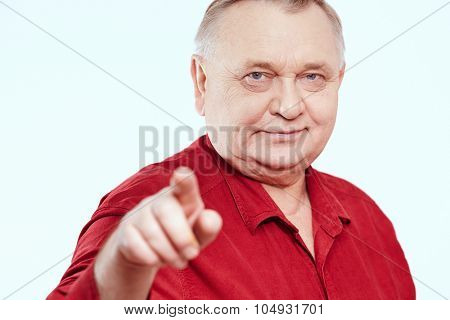 Close up portrait of aged man wearing red shirt standing and pointing at camera with his index finger against white background - choice concept