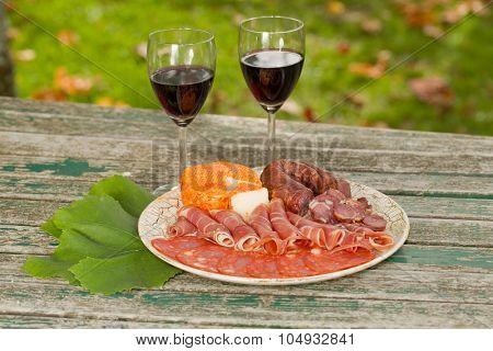 Country life setting with wine, cheese and meat