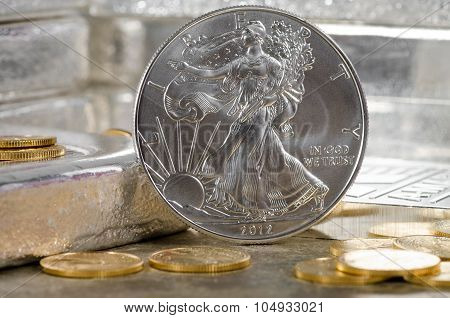 United States Silver Eagle With Gold Coins & Silver Bars In Background