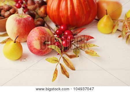 colorful leaves, pumpkins, apples on wooden background