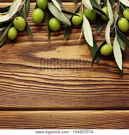 green olives over wooden background