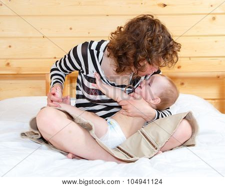 Mother In Lotus Position Holds Her Cute Baby