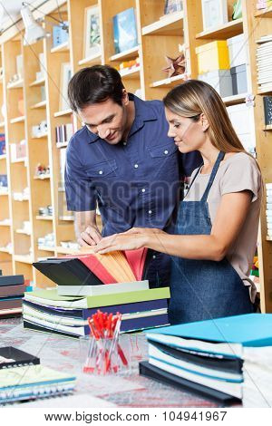 Mid adult saleswoman assisting male customer to choose envelop in shop