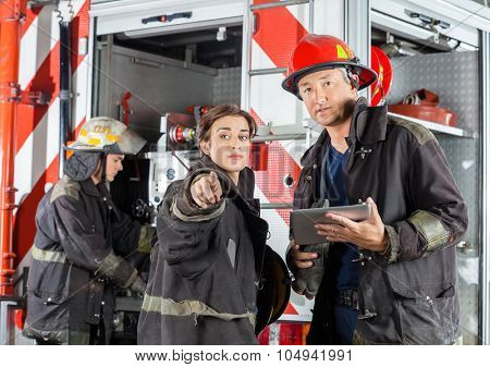 Female firefighter showing something to colleague holding digital tablet against truck at fire station